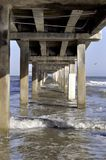 Under The Pier. The long view underneath a pier on North Padre Island, Corpus Christi, Texas. Spring Day at the beach during Spring Break with a bird in the Royalty Free Stock Photography