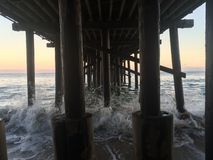 Under the pier in Malibu California. At sunset. Sand, surf, wave Royalty Free Stock Photography