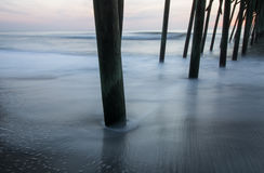 Under the Pier. The sky lightens in the east as the tide recedes under the Kure Beach Pier Royalty Free Stock Photos