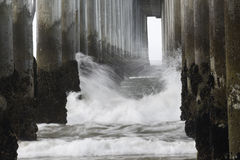 Under the Pier. Splashing water from the ocean Stock Photos
