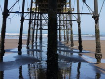 Under The Pier. Underneath Victorian Pier looking towards a blue ocean on a clear summers day Stock Photo