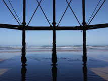 Under The Pier. Underneath Victorian Pier looking towards a blue ocean on a clear summers day Royalty Free Stock Photos