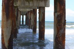 Under the Pier. View under a pier with strong current of the sea Stock Photos