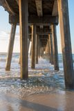 Under the Pier. Waves crashing into the pylons under the pier in Pensacola Florida royalty free stock photos