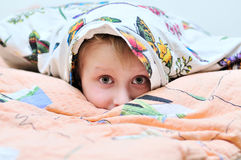 Under the pillow. Little boy laying under the pillow and watching something frightful on TV Stock Photography