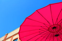 Under pink sun umbrella. Low-angle shot of a bright pink sun umbrella in the city against a clear blue sky. Spending shade in summer Royalty Free Stock Photography