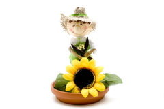 Under plate with straw doll and sunflower Stock Photos