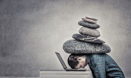 Under pressure of work. Woman programmer pressed with heavy stone to laptop royalty free stock photography