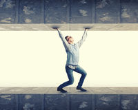 Under pressure. Young troubled businessman trapped between two walls Royalty Free Stock Images