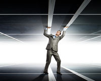 Under pressure. Young troubled businessman trapped between two walls Stock Photos