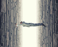 Under pressure. Young troubled businessman trapped between two walls Royalty Free Stock Photos