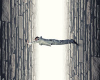 Under pressure. Young troubled businessman trapped between two walls Stock Images