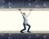 Under pressure. Young troubled businessman trapped between two walls Stock Photography