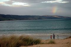 Under the Rainbow. A family on the beach with a rainbow above them Stock Images