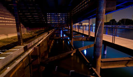Under the Riverwalk. Night lights casting slots of light onto supports under the Riverwalk in Milwaukee's Third Ward Royalty Free Stock Image