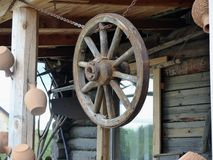 Obsolete old wheel of the horse cart. Hanging under the roof of a rural hut. Retro. Closeup. Ural, Russia.   Royalty Free Stock Photography