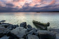 Under the rosy clouds were wooden sailboats and ro Stock Photo