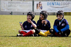 Under 12 rugby players sitting on the pitch waiting for the next coach's call Royalty Free Stock Photography
