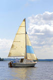 Under the sail. Boat with the sail swimming on the river along the coast Royalty Free Stock Photography