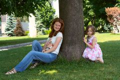 Under the shade of tree. Mother with daughter sitting under the shade of big tree at the park stock photo