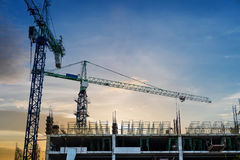 Under site construction building with cranes in sunset. Under construction building with cranes in sunset Royalty Free Stock Photo