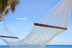 Under the sky. View of nice white hammock hanging between two palms stock photo