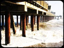 Under Southwold pier on a cold winter day. Rough sea under the pier in Southwold Stock Image