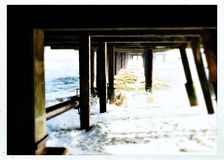 Under Southwold pier on a cold winter day. Rough sea under the pier in Southwold Royalty Free Stock Photography