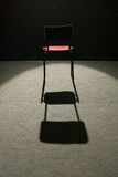 Under spotlight. One red chair on stage, lighted with one spot light, empty seats in background Royalty Free Stock Photography