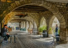 Under a stone archway. Villefranche de Rouergue, Midi Pyrenees, France - September 16, 2017: Old passage under a stone archway with some people walking Stock Photos