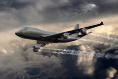 Under the storm. A 747 Boeing flying through dark clouds under the storm. A lightning crosses the sky in the background Royalty Free Stock Images