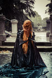 Under the storm, Beautiful vampire woman in palace gate, gothic Stock Photo