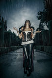 Under the storm, Beautiful vampire woman in palace gate, gothic. Fantasy huge coat Stock Photos