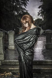 Under the storm, Beautiful vampire woman in palace gate, gothic. Fantasy huge coat Royalty Free Stock Images
