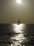 Under the sun. Sailing yacht in a light breeze backlighted by a golden evening sun Royalty Free Stock Image