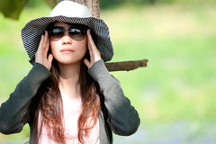 Under the sun. A girl stands under a tree wearing sunglasses Royalty Free Stock Images