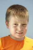 Under sun rays. Portrait of boy in orange t-shirt looking straight to camera Stock Image