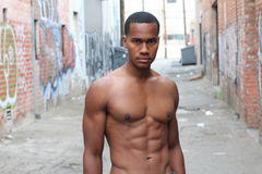 Under the sunshine, a masculine black guy, half naked, is standing by an alley with rough expression / Portrait of Young Black Fit Stock Photos