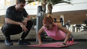 Under supervision of coach woman in a fitness club wringing out her arms. In gym, personal instructor follows the exercises of a female athlete stock footage