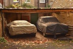 Under taket parkerade täckte bilar Fotografering för Bildbyråer