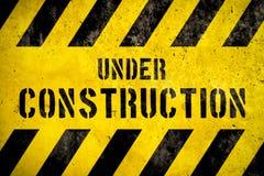 Under text för konstruktionsvarningstecken med gulingsvartband som målas över betongväggcementfasad som texturbakgrund arkivbild