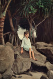 Under a tree on a large rock sits a boy Stock Images