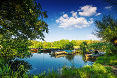 Under the trees, boats in the harbor at Lake Royalty Free Stock Images