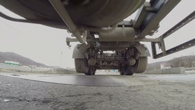 Under truck trailer ride over camera. A huge truck trailer rides over camera in asphalt with an iron platform for weighing stock footage