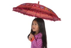 Under the Umbrella 1. A young asian girl huddles under her umbrella. isolated on white Royalty Free Stock Photos