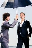 Under umbrella. Portrait of two successful business people under umbrella together Stock Images
