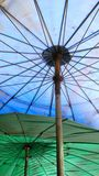 Under the umbrella shade. Under the blue and green big umbtrella shade background royalty free stock images