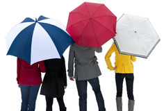 Under Umbrellas in the Rain. A group of colorful people standing together under their umbrellas to stay out of the rain or snow Royalty Free Stock Photos