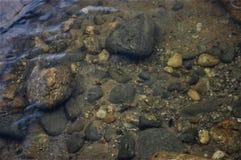 Under vattenklicken av stenar arkivfoto