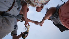 Under view of ginger man with moustache pouring champagne to his female friends stock video